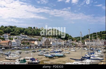The harbour at St Aubin in Jersey.  The marina of small craft are aground at low tide and buildings surround the harbour. - Stock Photo