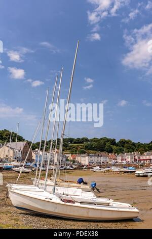 The harbour at St Aubin in Jersey. Yachts are aground at low tide and buildings ring the habour. - Stock Photo