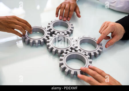Close-up Of Business People's Hand Connecting Gears On Desk - Stock Photo