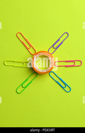 Cellophane tape circled with colored paper clips. Scotch tape - Stock Photo