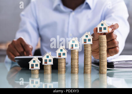 Close-up Of A Business Person Placing Miniature House Model On Stacked Coins