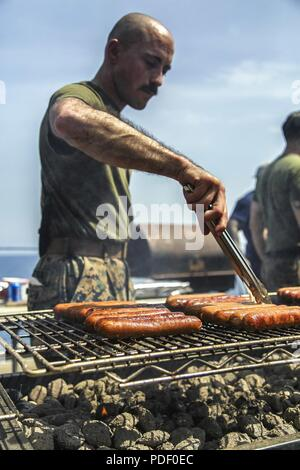 MEDITERRANEAN SEA (May 20, 2018) U.S. Marine Corps Staff Sgt. Ryan Bartolo, a platoon sergeant assigned to 1st Rifle Platoon, Fox Company, Battalion Landing Team, 2nd Battalion, 6th Marine Regiment, 26th Marine Expeditionary Unit (MEU), grills hotdogs a U.S. Navy's Morale, Welfare and Recreation event known as Steel Beach aboard the Harpers Ferry-class dock landing USS Oak Hill (LSD 51) in the Mediterranean Sea, May 20, 2018. The Oak Hill, homeported in Virginia Beach, Virginia, and the 26th MEU are conducting naval operations in the 6th Fleet area of operations. (Marine Corps - Stock Photo