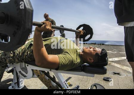 MEDITERRANEAN SEA (May 20, 2018) U.S. Marine Corps Sgt. Romeo L. Sarmiento III, an assault section leader assigned to Weapons Platoon, Fox Company, Battalion Landing Team, 2nd Battalion, 6th Marine Regiment, 26th Marine Expeditionary Unit (MEU), competes in a physical training challenge during a U.S. Navy's Morale, Welfare and Recreation event known as Steel Beach aboard the Harpers Ferry-class dock landing USS Oak Hill (LSD 51) in the Mediterranean Sea, May 20, 2018. The Oak Hill, homeported in Virginia Beach, Virginia, and the 26th MEU are conducting naval operations in the 6th Fleet area of - Stock Photo
