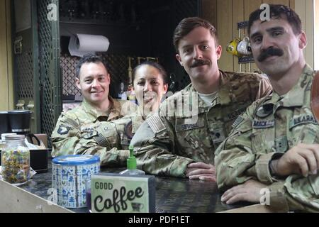CAMP TAJI MILITARY COMPLEX, Iraq – (from left to right) U.S. Army Chief Warrant Officer 2 Ryan Amato, Capt. Ashley Morris, Spc. Toby Sewell and Chief Warrant Officer 2 David Mack assigned to 1st Battalion, 189th Aviation Regiment stand behind the Dustoff Coffee shop bar at Camp Taji, Iraq, May 18, 2018. Creating or taking over a coffee shop while deployed is an Oregon National Guard tradition. The donation-based business provides funds for Soldiers in order to boost morale and build unit cohesion. - Stock Photo