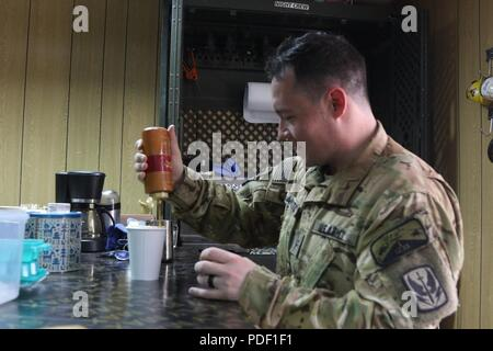 CAMP TAJI MILITARY COMPLEX, Iraq – U.S. Army Chief Warrant Officer 2 Ryan Amato assigned to 1st Battalion, 189th Aviation Regiment, prepares a caramel latte at the Dustoff Coffee shop at Camp Taji, Iraq May 18, 2018. The Dustoff Coffee shop is a donation-based business that provides funds for Soldiers in order to boost morale and build unit cohesion. - Stock Photo