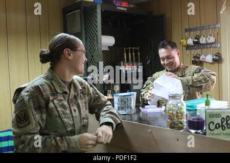 CAMP TAJI MILITARY COMPLEX, Iraq – U.S. Army Chief Warrant Officer 2 Ryan Amato assigned to 1st Battalion, 189th Aviation Regiment, prepares an iced coffee for Spc Sarah Morris at the Dustoff Coffee shop at Camp Taji, Iraq May 18, 2018. The Dustoff Coffee shop is a donation-based business that provides funds for Soldiers in order to boost morale and build unit cohesion. - Stock Photo
