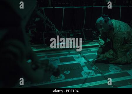 An aircrew member of a C-130J Super Hercules assigned to the 774th Expeditionary Airlift Squadron at Bagram Airfield, Afghanistan, tightens down chains on a High Mobility Artillery Rocket System (HIMARS) on May 15, 2018. The C-130J is capable of operating from rough, dirt strips and is the prime transport for airdropping troops and equipment into hostile areas. The flexible design enables a C-130 to fit a HIMARS with additional equipment and passengers in its cargo . - Stock Photo