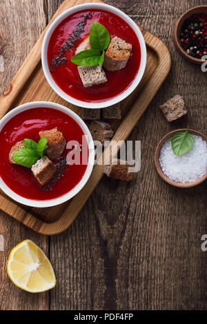 Traditional tomato soup garnished with rye bread croutons and thyme, top view - Stock Photo