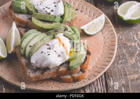 Poached egg and sliced avocado on whole wheat bread toast served with lime on ceramic plate on rustic wooden table, vegetarian sandwiches - Stock Photo