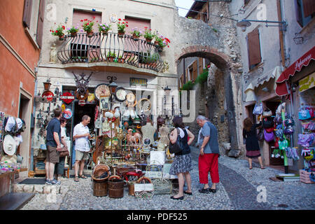 Tourists at a souvenir shop, old town of Malcesine, province Verona, Garda lake, Lombardy, Italy - Stock Photo
