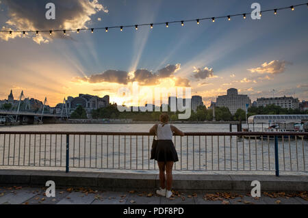 LONDON, UK - AUGUST 6, 2018 :  A young woman on the South Bank of the River Thames looks at the Crepuscular rays as the sun sets behind Charing Cross