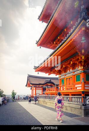 A Japanese girl in summer yukata kimono dress walks by Sanjunoto Pagoda on the grounds of Kiyomizu-dera Temple (Kiyomizudera) in Kyoto, Japan. - Stock Photo