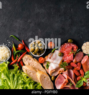 Antipasto set platter on black stone background. Cold smoked meat plate with sausage,sliced ham, bacon, olives, bread, cheese and herbs. Appetizer variety with copy space. Top view or flat lay. Square - Stock Photo