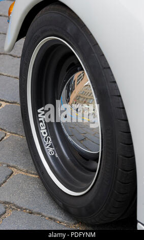Wheel and reflections of Customised black and white Volkswagen Beetle parked on a street in Prague - Stock Photo