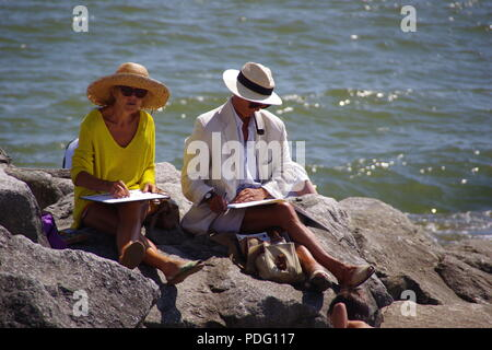 Elderly Couple in Traditional Smart Summer Clothing Sketching at the Seaside, The Gentleman Smoking a Pipe. Sidmouth Folk Festival, East Devon, UK. - Stock Photo