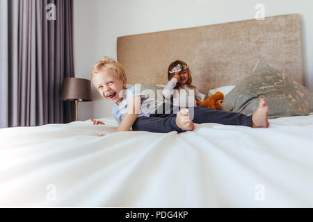 Happy kids playing in bedroom. Little boy smiling with girl at the back in crown on the bed. - Stock Photo