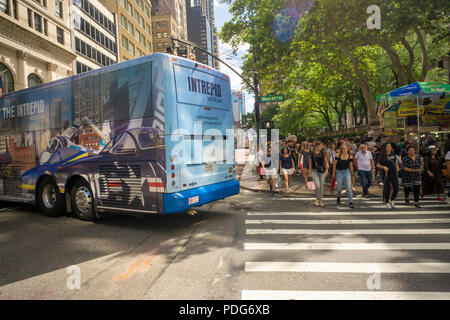 Pedestrians cross West 42nd Street as a bus turns onto Fifth Avenue in Midtown Manhattan in New York on Saturday, August 4, 2018. (© Richard B. Levine) - Stock Photo