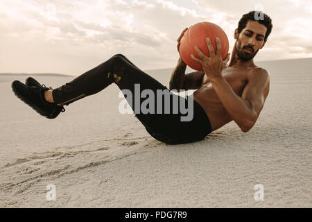 Strong young man doing a medicine ball workout on sand dunes. Athlete using a medicine ball for fitness training at desert. - Stock Photo