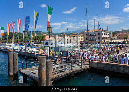 Tourists waiting for excursion boat at the pier of Bardolino, province Verona, Lake Garda, Lombardy, Italy - Stock Photo