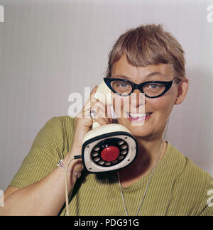 1950s glasses and telephone. A young woman in typical fifties glasses and bows is talking on the telephone.  Swedish on-piece plastic telephone created by Ericsson Company of Sweden. Because of its styling and its influence on future telephone design, the Ericofon is considered one of the most significant industrial designs of the 20th century. The idea was to incorporate the dial and handset into one single unit. The model is also known as the Cobra telephone for its resemblance to a coiled snake, and is now a sought after antique. - Stock Photo