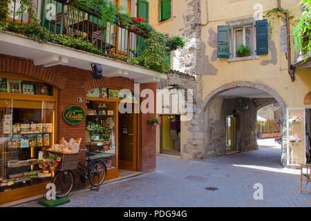 Bicycle with a basket full with bread, decoration in front of a bakery shop, alley at old town of Garda, province Verona, Lake Garda, Lombardy, Italy - Stock Photo