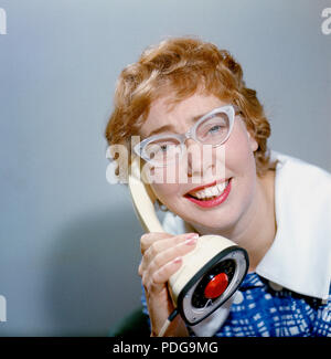 1950s glasses and telephone. A young woman in typical fifties glasses and bows is talking on the telephone.  Swedish on-piece plastic telephone created by Ericsson Company of Sweden and launched 1956. Because of its styling and its influence on future telephone design, the Ericofon is considered one of the most significant industrial designs of the 20th century. The idea was to incorporate the dial and handset into one single unit. To call, you lifted it up and dialed the number, and to end the call, you put the phone down.  The model is also known as the Cobra telephone for its resemblance to - Stock Photo