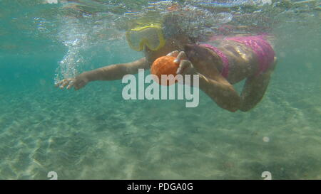 Happy baby girl in snorkeling mask dive underwater with toy in sea. Healthy lifestyle, people water sport outdoor adventure, swimming lessons on summer beach family holidays with child - Stock Photo