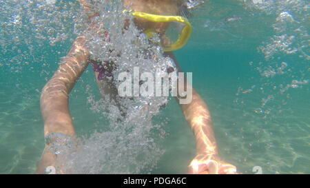 Portrait of little girl swimming underwater in sea. Cute girl in mask creates bubbles under water.Summer vacation. Small girl has fun. Copy space - Stock Photo