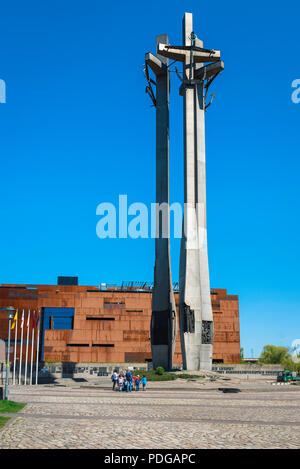 View of the 42 metre tall Monument To The Fallen Shipyard Workers in Gdansk, with the European Solidarity Centre Museum building at rear, Poland. - Stock Photo