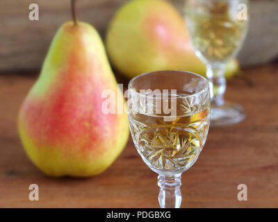 Pear liqueur in crystal glasses and pears on wooden background - Stock Photo