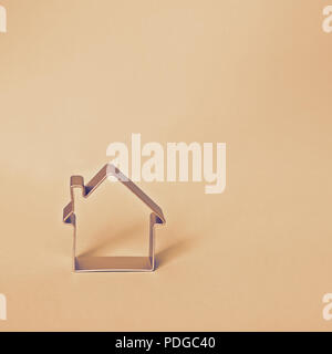 Simple shape of small house isolated on beige background with copy space, square format - Stock Photo