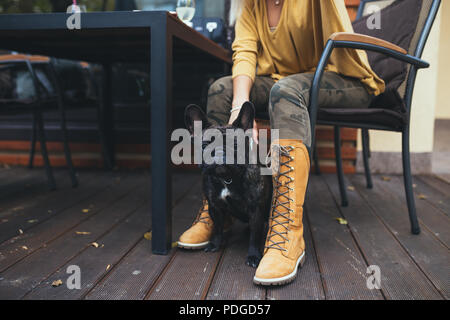 Beautiful and happy blonde woman with tablet enjoying in cafe bar with her adorable French bulldog. - Stock Photo
