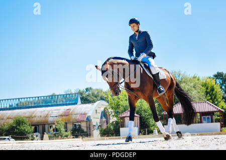 Young promising equestrian feeling exhausted after training - Stock Photo