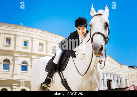 Black-eyed beaming female rider leaning on her devoted white horse - Stock Photo