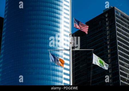 3 flags flying in front of skyscraper, New York City - Stock Photo