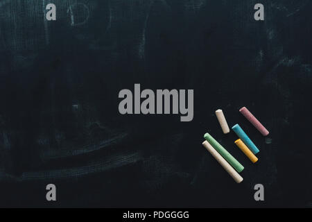Colorful chalk on blackboard, concept of creativity and education - Stock Photo