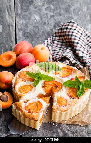 Homemade  cheese cake with apricot on wooden table - Stock Photo