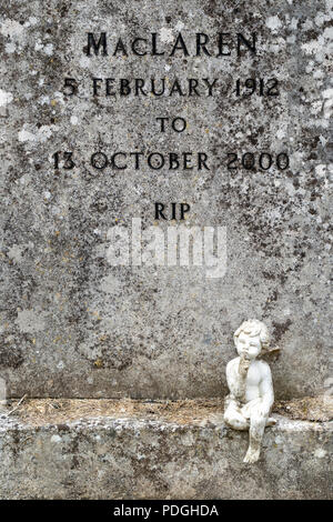 Small statue sitting at the base of grave stone - Stock Photo