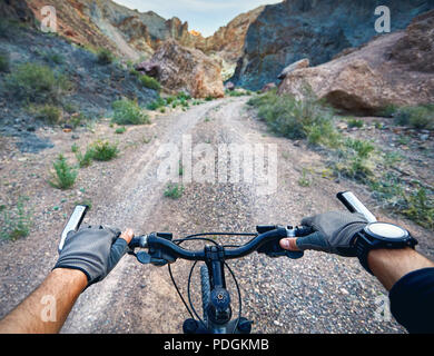 Rider in gloves holding handlebars of mountain bike in the desert canyon. Extreme Sport Concept. - Stock Photo