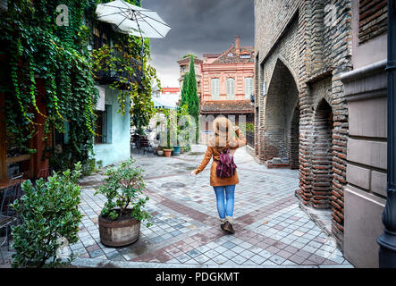 Tourist woman in brown hat walking down old the Old streets of central Tbilisi, Georgia - Stock Photo