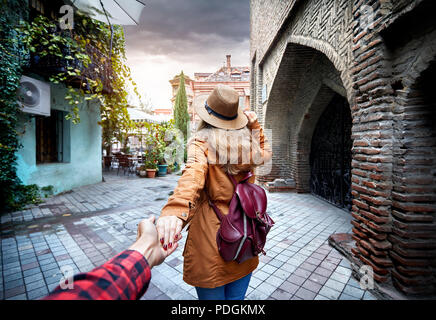 Woman in hat and brown jacket leading man to the narrow street in old, Georgia - Stock Photo