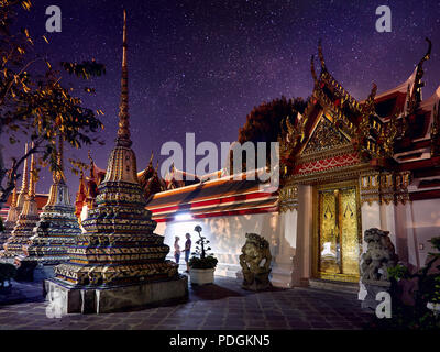 Young Couple in Buddhist temple complex Wat Pho in Bangkok at magical night starry sky at background in Thailand - Stock Photo