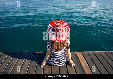 Woman in hat and striped dress sitting on pier and looking the emerald blue sea. Summer and Sea concept. - Stock Photo
