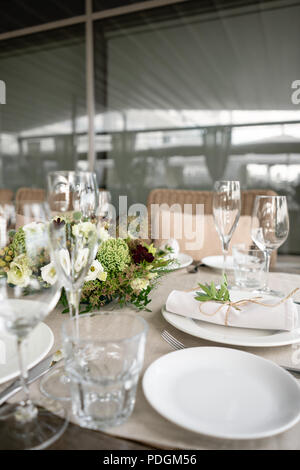 Wedding Banquet or gala dinner. The chairs and table for guests, served with cutlery and crockery. Covered with a linen tablecloth runner. party on terrace - Stock Photo