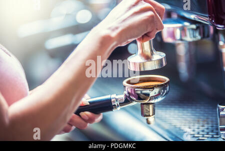 Barista woman making an espresso coffee with portafilter and coffee tamper. - Stock Photo