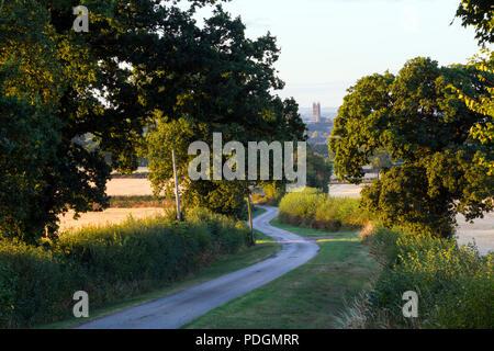 Early morning view along a winding country lane towards St. Mary`s Church, Warwick, Warwickshire, UK - Stock Photo