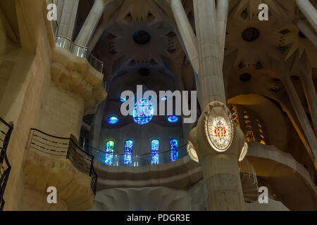Architectural details of blue stained glass window and Barcelona lamp on column inside Sagrada Familia - large unfinished Roman Catholic church in Bar - Stock Photo