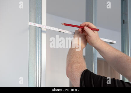 A man holding a pencil with measure against metal frame. Maintenance works indoors in the flat. - Stock Photo