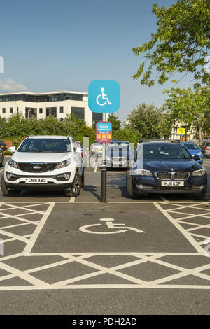 Signpost and markings on the ground to denote a parking bay reserved for disabled persons - Stock Photo