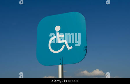 Blue metal sign with disability symbol above a parking bay in a supermarket car park reserved for disabled persons - Stock Photo